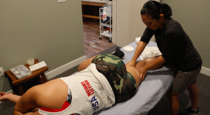 Manual sports injury rehab on weightlifter